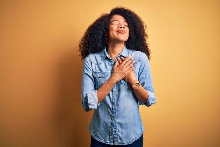 Photo pour Jeune Africaine américaine aux cheveux afro sur fond jaune et isolé, souriante avec les mains sur la poitrine avec les yeux fermés et geste reconnaissant sur le visage. Concept de santé. - image libre de droit