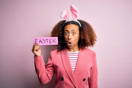 African american woman with afro hair wearing bunny ears holding paper with message scared in shock with a surprise face, afraid and excited with fear expression