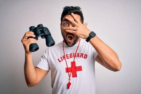 Foto de Hombre joven de salvavidas con barba vestida de camiseta con cruz roja y gafas de sol usando pelaje de silbato en choque cubriendo cara y ojos con la mano, mirando a través de los dedos con expresión embarazosa.. - Imagen libre de derechos