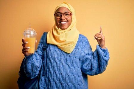 Foto de Una joven afroamericana de nacionalidad afroamericana que lleva un hijab musulmán bebiendo zumo de naranja sorprendida con una idea o pregunta señalando con el dedo con la cara feliz, la número uno. - Imagen libre de derechos