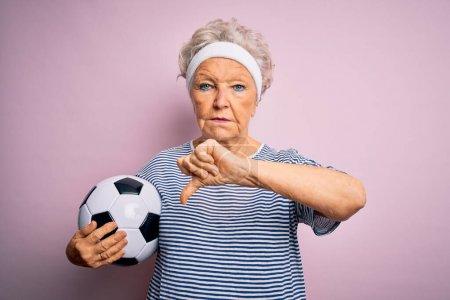 Foto de Alta mujer de pelo gris hermosa sosteniendo balón de fútbol de pie sobre fondo rosa con cara enojada, signo negativo que muestra disgusto con los pulgares hacia abajo, concepto de rechazo. - Imagen libre de derechos