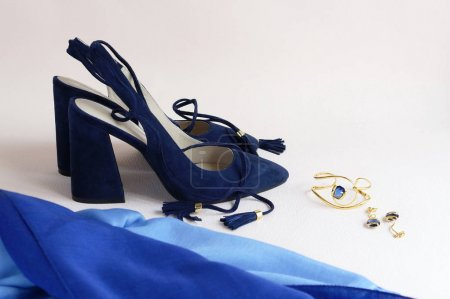 Beautiful woman fashion blue high heel shoes, jewelry and silk scarf on light background