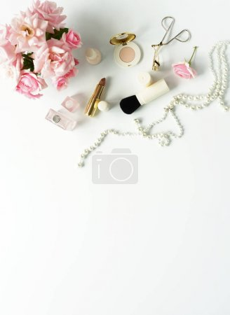 Flat lay, top view feminine desk, female make up accessories and bouquet roses.Beauty blog concept.Copy space