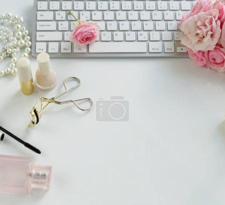 Flat lay, top view office feminine desk, female make up accessories, workspace with laptop and bouquet roses.Beauty blog concept.Copy space