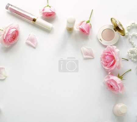 Flat lay, top view feminine desk, workspace , female make up accessories and bouquet roses.Beauty blog concept.Copy space