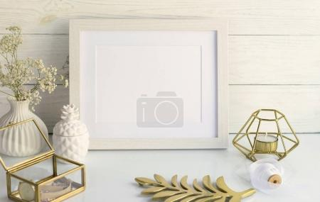 White frame mockup with interior items on white wooden background. Poster product design styled mock-up.Copy space