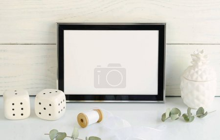 Black frame mockup with interior items on white wooden background. Poster product design styled mock-up.Copy space