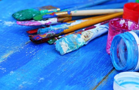 brushes and paints on a blue wooden background. Vintage
