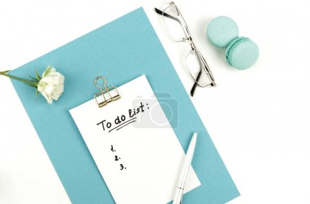 """to do list"" is written on notepad with pen on office table, glasses, white rose"
