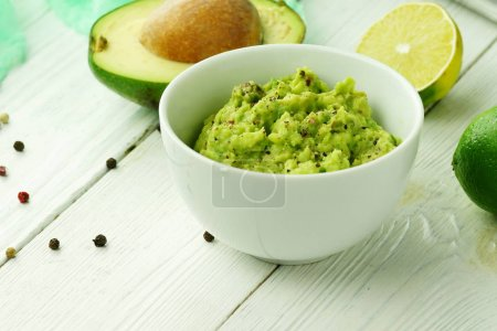 Traditional latinamerican mexican homemade sauce guacamole in white bowl, cut half avocado and lime on white wooden table.