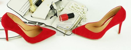 Female fashionable stylish accessories and cosmetics. red shoes with heels, white bag, watch, glasses, lipstick, mascara, red nail polish on a white background. Beauty blog concept. Copy space