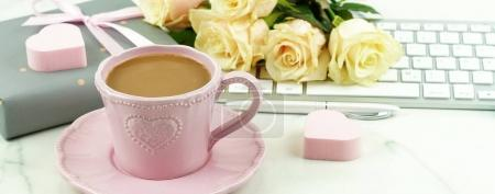 Valentine's day concept. Pink cup with cocoa, a bouquet of beautiful roses, a keyboard and a gift with pink hearts. Copy space