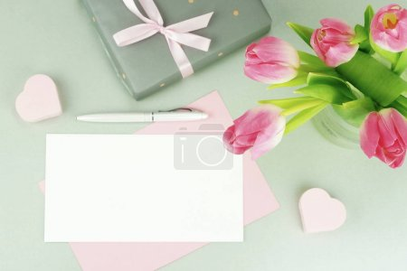Photo for Feminine desk, workspace with a bouquet of beautiful pink tulips in a vase, a gift and a card for text on a gray background. flat lay. top view. copy space - Royalty Free Image