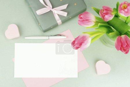 Photo pour Bureau féminin, espace de travail avec un bouquet de belles tulipes roses dans un vase, un cadeau et une carte pour le texte sur un fond gris. Pose plate. vue de dessus. espace de copie - image libre de droit