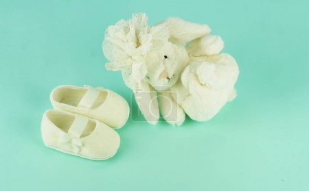 Waiting for baby. white ballet shoes for newborn and banny on a pastel blue background. copy space