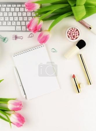 Flat lay, top view office feminine desk, female make up accessories, workspace with laptop, cup of coffee. notebook and bouquet pink tulips.Beauty blog, Holidays concept.Copy space