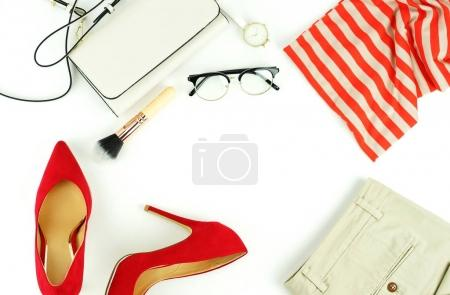 flat lay feminine clothes and accessories collage with blouse, trousers, glasses, watch, red high heel shoes on white background.Copy space. Top view