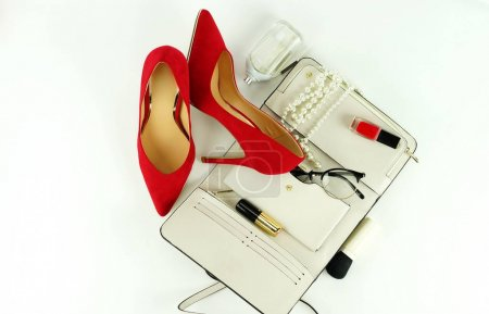 Female fashionable stylish accessories and cosmetics. red shoes with heels, white bag, perfume, glasses, lipstick, red nail polish on a white background. Beauty blog concept. Top view. Flat lay