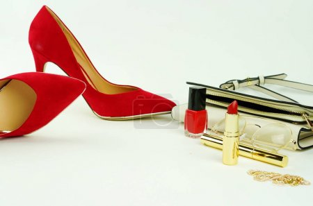 Female fashionable stylish accessories and cosmetics bracelet, red shoes with heels, white bag, glasses, lipstick, mascara, red nail polish on a white background. Beauty blog concept.