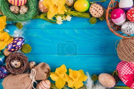 Easter eggs in nest on rustic wooden planks painted in blue. Easter concept. Flat lay.