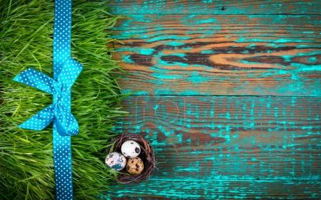 Easter eggs in nest on rustic wooden planks. Easter concept. Flat lay.