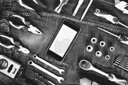 Smartphone and construction tools with blank for sign, top view, flat lay. Tools sailing and workers concept.