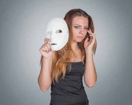 Young emotional woman holding mask in a hands pose in studio on