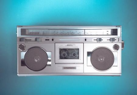 Old retro blaster cassette tape recorder on table in front backg
