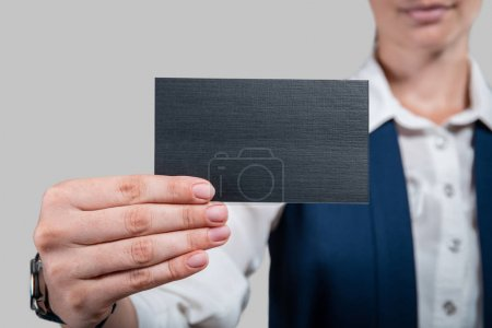 Business woman holding card in hands on gray background. Studio