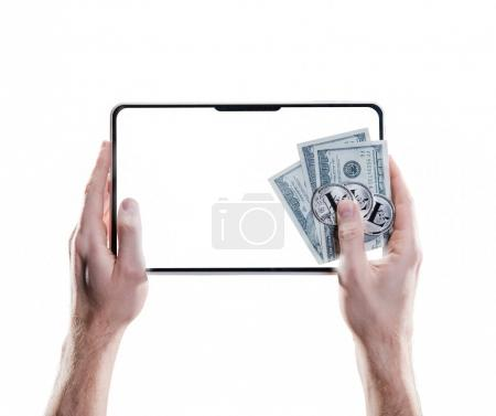 Hands holding mobile tablet with empty screen and bitcoin coins, dollar bills on the white background. Digital monitoring, checking and money exchange cryptocurrency concept