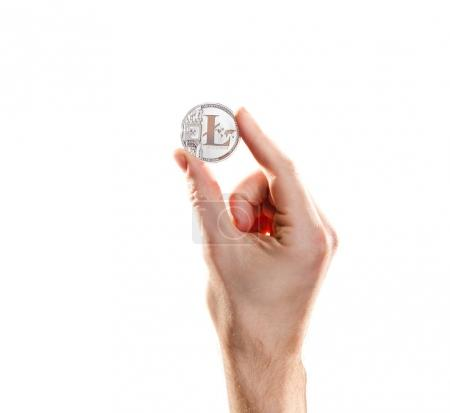 Hand with coins of litecoins against the backdrop of flying coins. Digital money exchange cryptocurrency concept