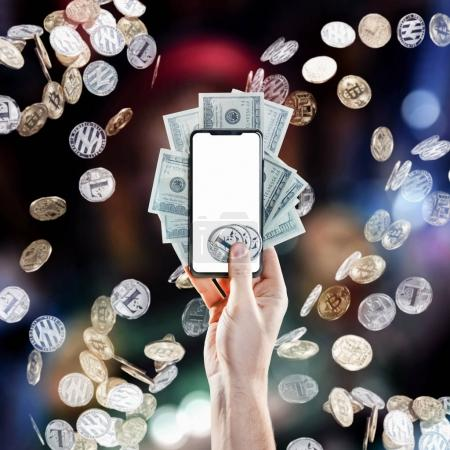 Hand holding mobile phone with empty screen and litecoin coins, dollar bills against the backdrop of flying coins. Digital monitoring, checking and money exchange cryptocurrency concept