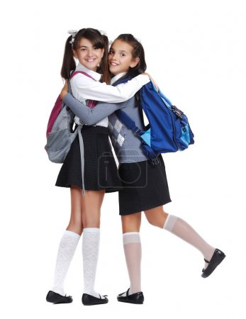 Photo for Two happy schoolgirls hugging as friends against white background - Royalty Free Image