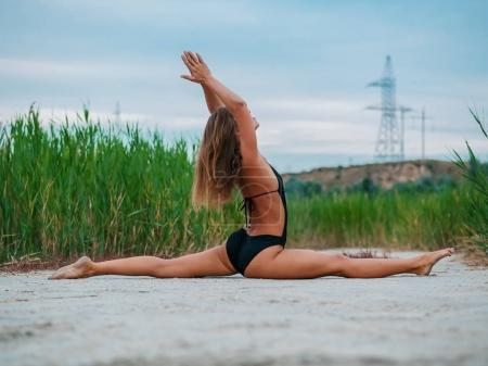Morning exercise. Twine. Woman stretching hip, hamstring muscles and groin area. Fit fitness athlete girl exercising sports stretches in black swimsuit at sunset near reeds.