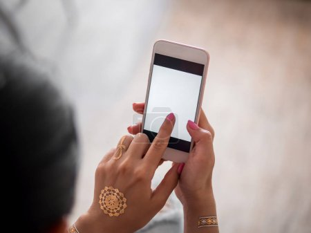 Woman with smartphone at home. Hands of young girl with flash tattoo using mobile device.