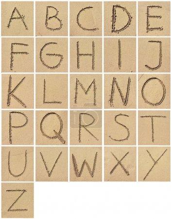 Photo pour Lettres de l'alphabet, écrit dans le sable. - image libre de droit