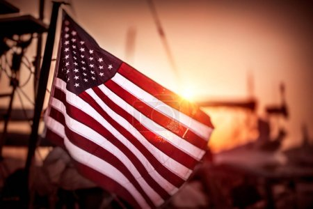 Photo for Flag of United States of America flutters in the winds in mild sunset light, independence day of America - Royalty Free Image