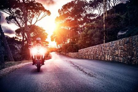Motocycliste dans la lumière du coucher du soleil