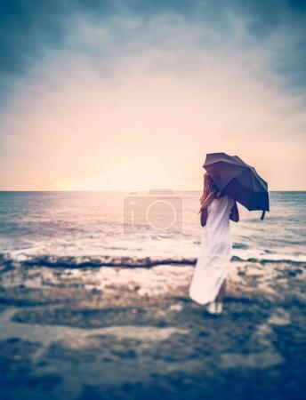 Photo pour Concept de la tristesse, la vue arrière d'une femme à l'ombrelle sur la plage, la jeune fille par temps couvert, donnant sur la mer orageuse, solitude - image libre de droit