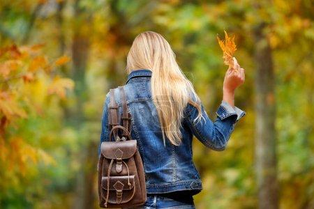 Photo pour Vue arrière d'une fille blonde marchant dans la forêt, tenant à la main des feuilles d'arbre sèches, s'amusant dans le parc d'automne - image libre de droit