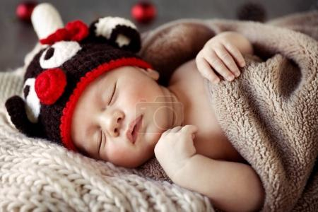 Photo for Cute baby wearing reindeer hat and sleeping at home in Christmas pajamas, funny costume for little child for winter holidays party, happy Christmastim - Royalty Free Image
