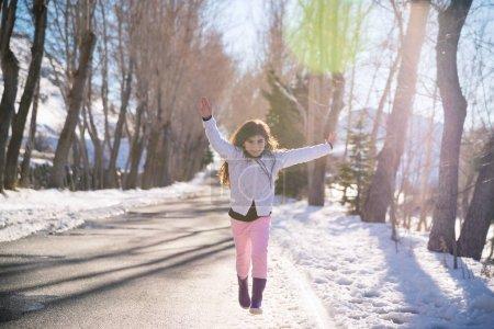 Photo pour Pistes de fille heureuse et saute vers le haut du bonheur, belle écolière souriant avec ressuscités mains appréciant temps ensoleillé chaud dans le parc d'hiver, vacances d'hiver heureux, bébé en bonne santé embrasing vie, concept de bien-être - image libre de droit