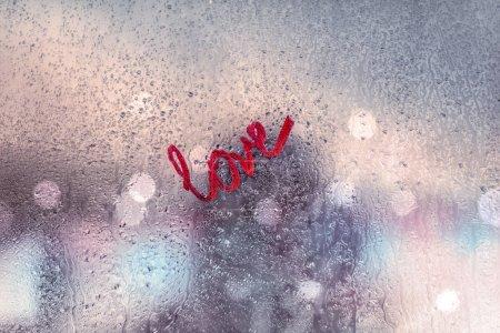 Photo pour Tout ce dont vous avez besoin est l'amour, message fort d'amour, fenêtre urbaine couverte de gouttes de pluie, relations romantiques après un premier rendez-vous, amour et concept de passion - image libre de droit