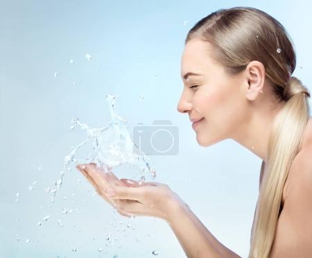 Photo pour Portrait de profil d'une jolie fille blonde avec plaisir à laver son visage dans la matinée par Claire rafraîchissante eau, parfait une peau propre, en utilisant anti acné remède, hygiène concep - image libre de droit