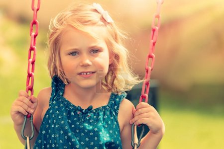 Photo for Cute baby girl swinging on swing outdoors, nice adorable child having fun on playground, happy carefree childhood concept - Royalty Free Image
