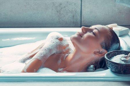 Photo pour Portrait d'une femme aux yeux fermés de plaisir prenant un bain à la maison, femme de plaisir prenant un bain avec une mousse, une journée au spa, concept d'hygiène et de relaxation - image libre de droit