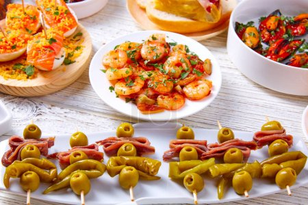 Photo for Tapas mix and pinchos food from Spain recipes also pintxos on a white wood board - Royalty Free Image