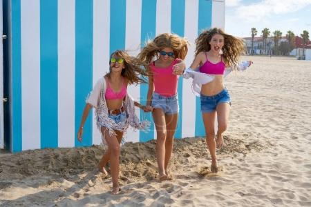 Photo for Best friends teen girls group running happy in a beach having fun - Royalty Free Image
