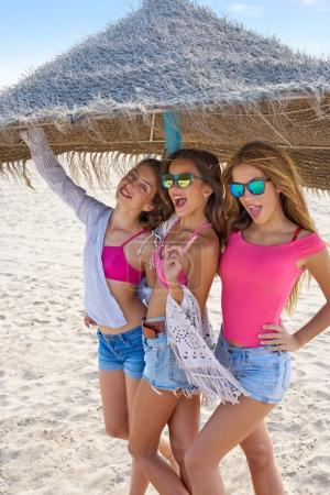 Photo for Teen best friends girls under thatch umbrella having fun on a beach - Royalty Free Image