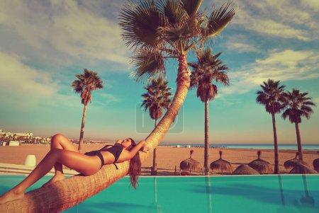 woman lying on pool bent palm tree trunk